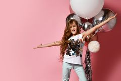 Teen girl in jeans and white shirt with her arms spreaded poses at fashion balloons act like singer or pop star at free text space. Happy young lady or teen girl royalty free stock photo