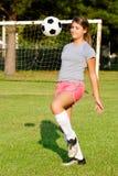 Teen girl juggling soccer ball Stock Images