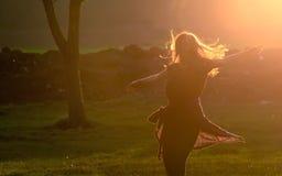 Teen girl jump against beautiful sunset Stock Photos