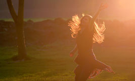 Teen girl jump against sunset in forest Royalty Free Stock Photography