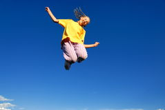 Teen girl jumping in air. A view of a young teenage girl wearing a bright yellow shirt as she jumps high into the air with a bright blue sky as a background Stock Photo