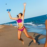 Teen girl jumping at ball on beach. Teen girl jumping at beach tennis ball outdoors Royalty Free Stock Images