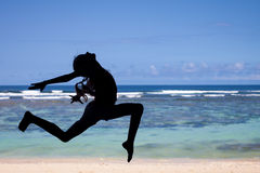Teen girl  jumping on the beach at blue sea shore in summer vaca Stock Image