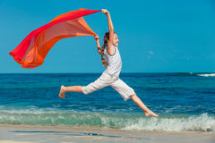 Teen girl  jumping on the beach at blue sea shore in summer vaca Stock Photography