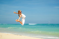 Teen girl  jumping on the beach at blue sea shore in summer vaca Royalty Free Stock Photos