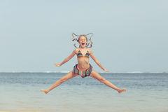 Teen girl  jumping on the beach at blue sea shore in summer vaca Stock Photo