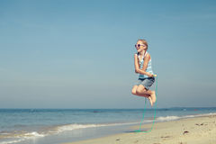 Teen girl  jumping on the beach at blue sea shore in summer vaca Royalty Free Stock Images
