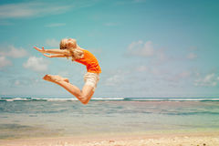 Teen girl  jumping on the beach Stock Photo