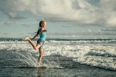 Teen girl  jumping on the beach at blue sea shore Stock Photography