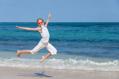 Teen girl  jumping on the beach at blue sea shore Royalty Free Stock Photography