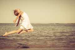 Teen girl jumping on the beach Stock Photo