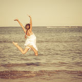 Teen girl jumping on the beach Stock Image