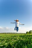 Teen girl jumping high in the field Stock Photo