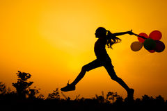 Teen girl jumping on the nature. Teen girl with balloons jumping on the nature of the evening Royalty Free Stock Photo