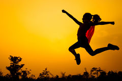 Teen girl jumping on the nature. Teen girl in superhero costume jumping in the evening on the nature Stock Photography