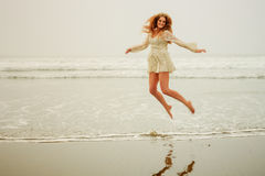 Teen girl jumping in the waves Royalty Free Stock Images