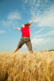 Teen girl jumping at a wheat field Royalty Free Stock Photo