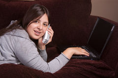 Teen girl on laptop. Pretty brunette teenage Hispanic girl laying on the sofa and typing on laptop and talking on a cordless phone royalty free stock photography