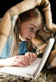 Teen girl with laptop. Serfing and hiding under blanket Stock Photography