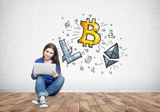 Teen girl with a laptop, cryptocurrency, bitcoin. Teen girl with a laptop wearing jeans and sitting on the floor in a concrete wall room with a cryptocurrency Royalty Free Stock Photos