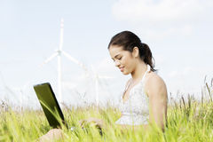 Teen girl with laptop next to wind turbine. Stock Photo