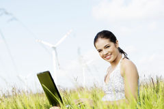 Teen girl with laptop next to wind turbine. Royalty Free Stock Photos