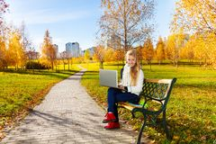 Teen girl with laptop in the park. Happy blond teen girl with long hair sitting with laptop in the autumn park Stock Image