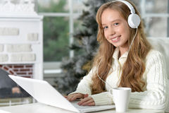 Teen girl with laptop. Portrait of teen girl in headphones with laptop Royalty Free Stock Photo