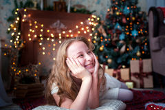 Teen girl laughing merrily on the Christmas garlands. Teen girl laughing merrily on the Christmas garlands Royalty Free Stock Images