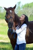A teen girl laughs with her horse. A teenage girl shares a laugh with her brown horse while standing out in a field Stock Image