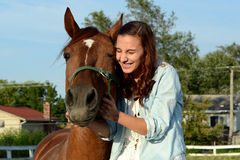 A teen girl laughs with her horse. A teenage girl shares a laugh with her brown horse Stock Photography