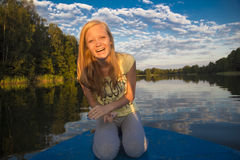 Teen Girl laughs traveling on boat in the lake Stock Images