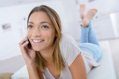 Teen girl laying on sofa talking on phone Stock Photos