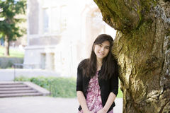 Teen girl leaning against large tree trunk Stock Photos