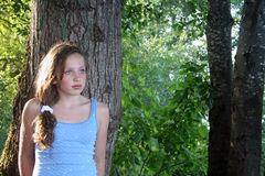 Teen Girl Leaning Against Tree. Beautiful young girl looking off into the distance while leaning against a tree Stock Photos