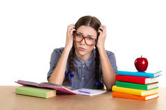 Teen girl  learning. Upset teens girl sitting at the table and holding her head, on the table lea many books, copybook and beautiful  red  apple, white Royalty Free Stock Photos