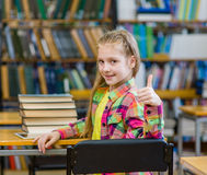Teen girl in library showing thumbs up Stock Photography