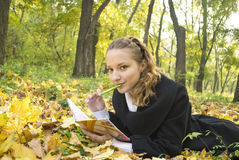 Teen girl lies in autumn park with her diary. Teen girl lies in gold autumn park with her diary Stock Image