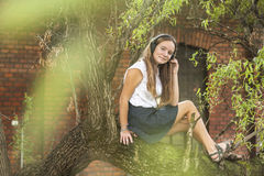 Teen girl listening to music with headphones while sitting on a tree. Stock Photo