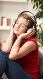 Teen girl listening to music at home. Teen girl listening to music on headphones with eyes closed smiling Royalty Free Stock Photo