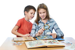 Teen girl and little boy with magnifier looking his stamp collec Royalty Free Stock Photo