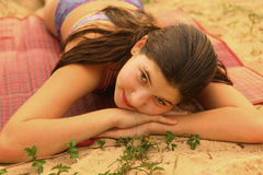 Teen girl with long brown hair close up photo. Lay on the beach Stock Images