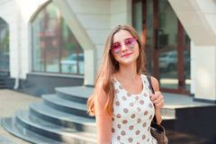 Girl with long brunette hair in pink heart-shaped sunglasses smiling outdoors stock photos