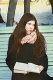 Teen girl with long dark hair with book sad. Sit on bench in park Royalty Free Stock Photo