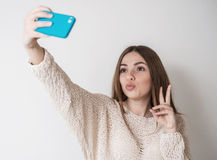 Teen girl with long hair makes selfie phone stock image