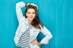 Teen girl with long hair posing like fashion model. On blue wall background Royalty Free Stock Image