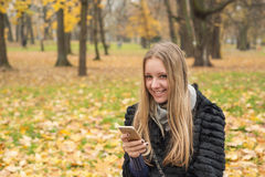 Teen girl with long hair sitting in the park in the fall with a smartphone Stock Photo