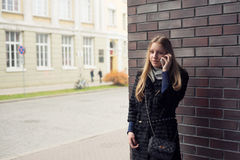 Teen girl with long hair talking on the phone outdoors in coat Stock Image