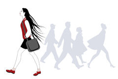 Teen girl with long hair in the wind walking on the street. Silhouettes of people in the background Stock Photo