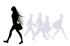 Teen girl with long hair in the wind walking on the street. Silhouettes of people in the background Royalty Free Stock Photo